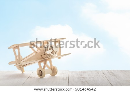 toy airplane on wood and sky background (retro filter)