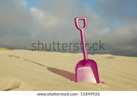 Toy beach shovel ready for play - stock photo