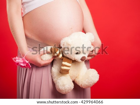 Toy bear cub against a stomach of the pregnant woman. The pregnant woman with a toy bear cub are walking on a meadow - stock photo