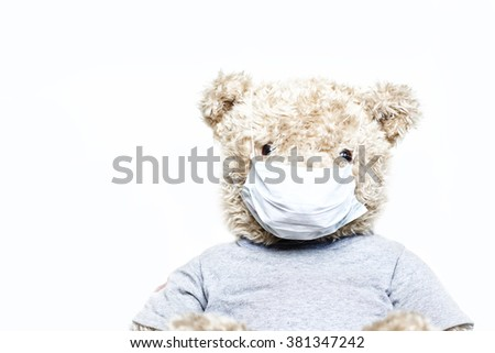 Toy bear in medical bandage on face isolated on white background - stock photo