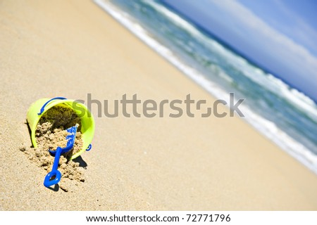 Toy bucket and shovel on an empty beach - stock photo