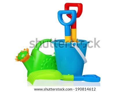Toy bucket, rake and spade isolated on white background - stock photo