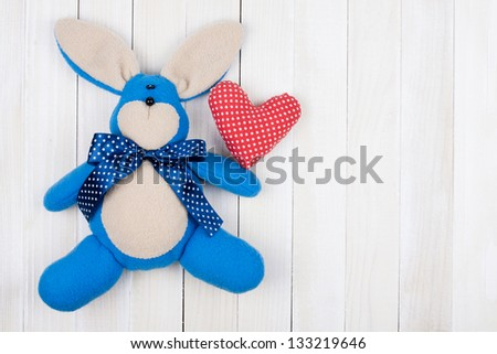Toy bunny, love heart on white wood background - stock photo