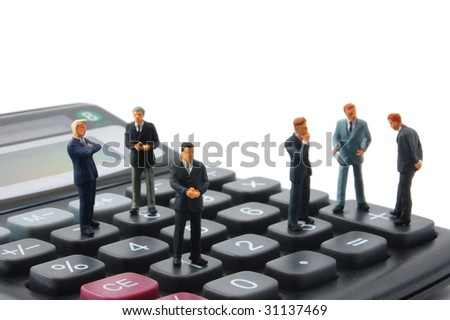 toy business man on calculator isolated on white background - stock photo