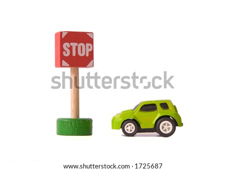 Toy Car parked next to a Toy Stop Sign - stock photo