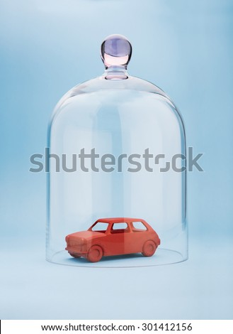 Toy car protected under a glass dome on blue background