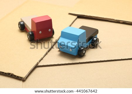 Toy car trucks on cardboard.   logistics image.  - stock photo