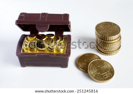 Toy chest full of gold coins and a pile of coins over white background. Toy chest and coins.