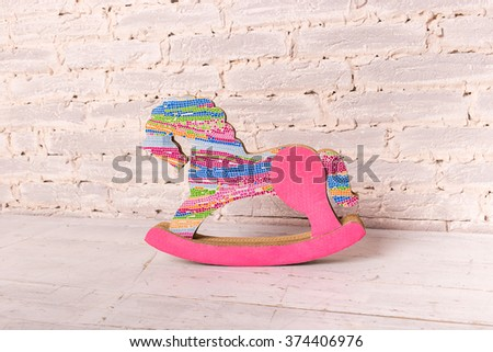 toy color rocking horse on the wooden floor in the brick wall background - stock photo