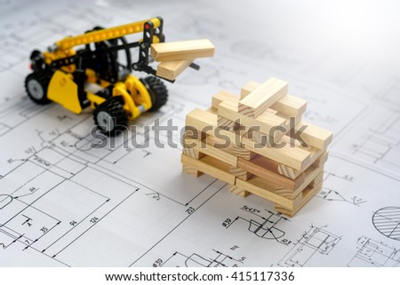 Toy construction machine buildsmodel of house from wooden blocks (bars) at the drawings - stock photo