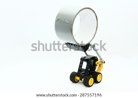 toy digger lifts duct tape - stock photo