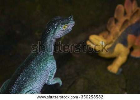 Toy dinosaur figurine in a real nature scenery outdoors.