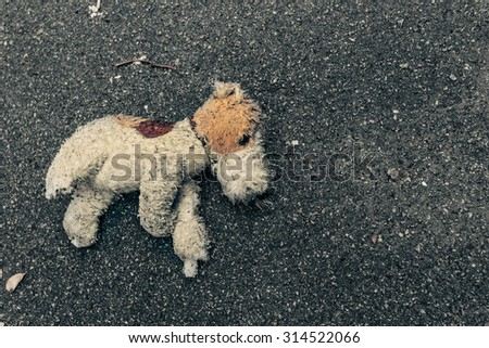 Toy dog abandoned on the pavement in the rain. Homeless concept. - stock photo