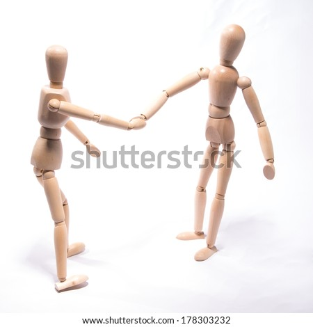 Toy dolls reaching out  for handshake - stock photo