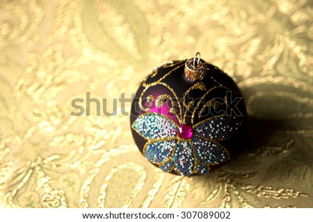 Toy. festive glitter christmas decoration bauble seasonal winter holidays. New year toy on light yellow background. Colored christmas ball toy - stock photo