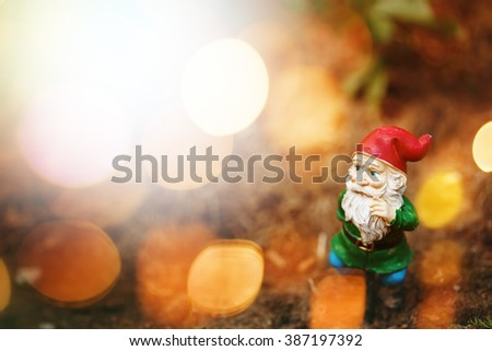 Toy Garden Gnome in Sun Light. Bokeh Lights Effect. Selective Focus, Space for Text. - stock photo