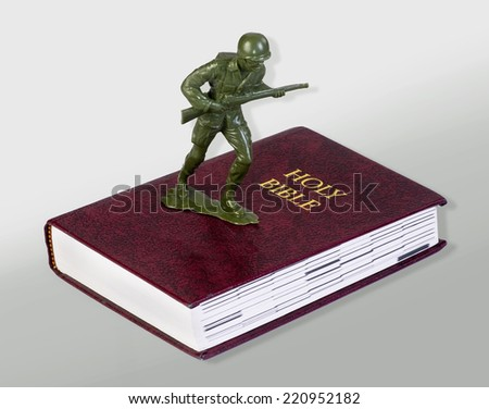 Toy green soldier standing on bible. - stock photo