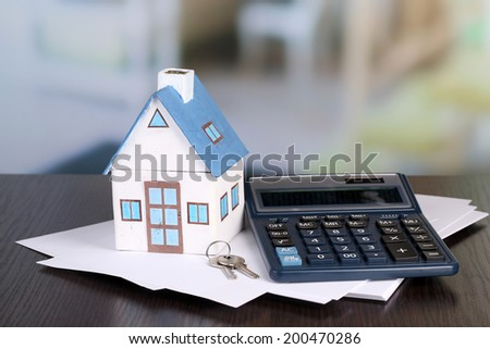 Toy house and calculator on table close-up - stock photo