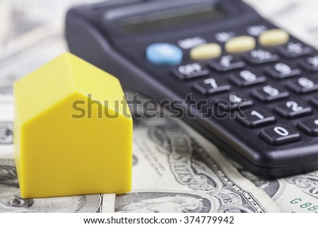 toy house and calculator on the background dollars banknotes - stock photo
