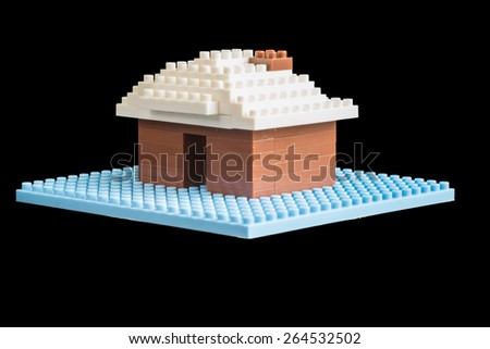 Toy house constructed of educational plastic building blocks on a blue base isolated on black conceptual of construction, real estate and ownership - stock photo