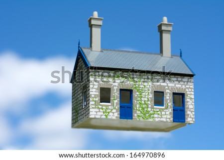 Toy house hover in the air aginst blue sky . Concept photo of Real estate market bubble , booming, money,price, rent, grid, home, house, housing, industry and subprime mortgage crisis. (Copy Space). - stock photo