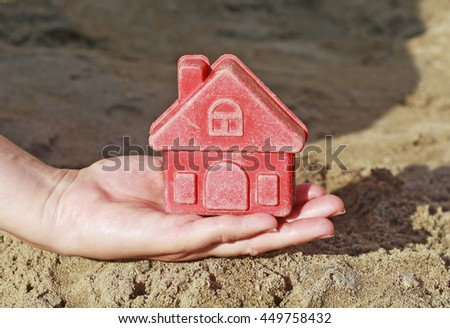 Toy house in the palm of a child. Bright plastic toys in the sandbox or on the beach. Sandbox, background, children, hand, home, house, buy, purchase, housing, business. Small house in a hand. - stock photo