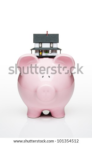 Toy house on a piggy bank - stock photo
