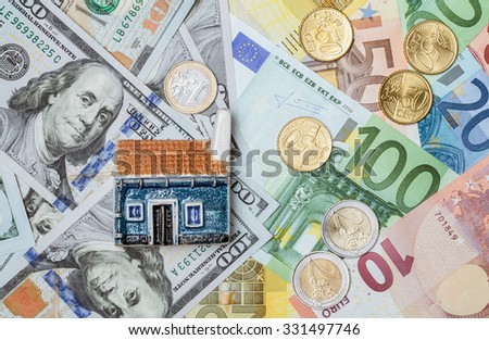 Toy house on many euro and dollar banknotes and euro coins- closeup shot - stock photo