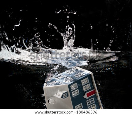 Toy house sinking underwater on a black background showing flooding concept - stock photo
