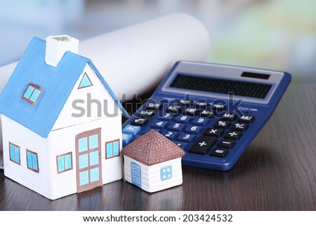 Toy houses and calculator on table close-up - stock photo