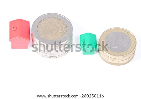 Toy houses on coins, on a white background - stock photo