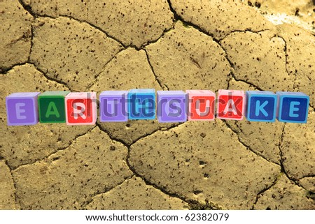 toy letters that spell earthquake against a barren land background with clipping path - stock photo