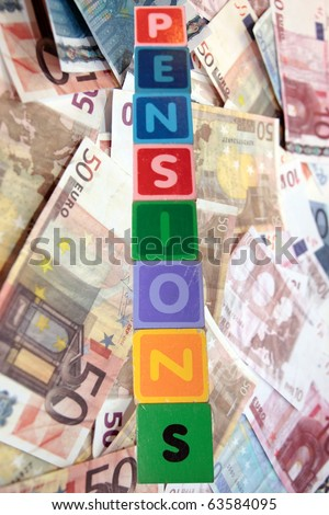 toy letters that spell pensions against a cash background with clipping path