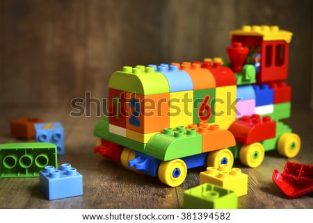 Toy made from multicolor blocks  on rustic background.