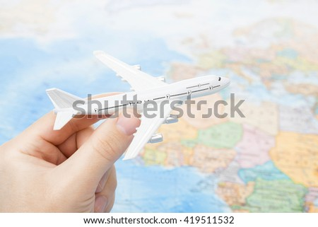 Toy plane in hand with world map on background - focus on the plane - stock photo