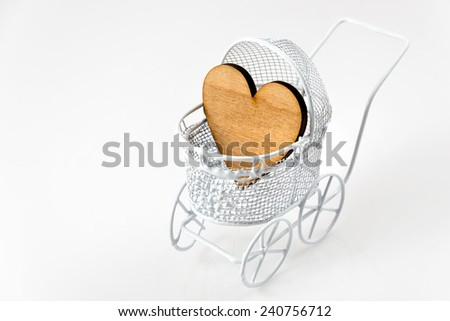 Toy pram with wooden heart isolated on white background with copy space for your message. Newborn greeting card - stock photo