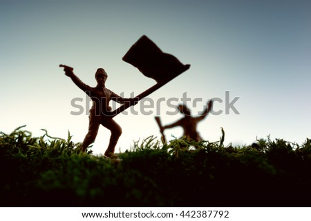 Toy soldier carrying flag and attacking - stock photo