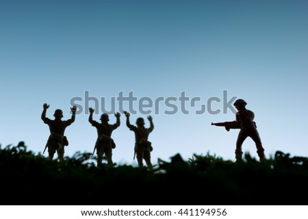 Toy soldiers surrender to an armed enemy - stock photo