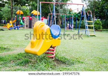 toy spring rocking in public playground  - stock photo