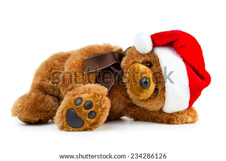 Toy teddy bear wearing a santa hat isolated on white background - stock photo