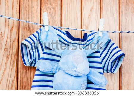 Toy teddy dog, puppy with baby clothing. Clean little child cloth hanging on rope in laundry. Blue cotton infant dry brown small toy. Birth newborn kid.   - stock photo
