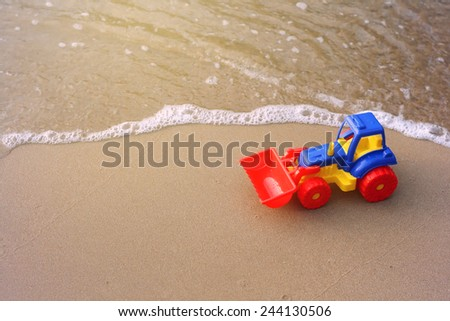 toy tractor on the sand beach toned photo selective focus soft - stock photo