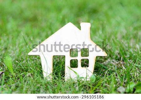 Toy wooden house on green grass background