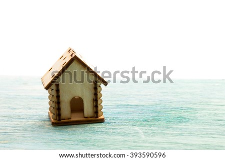 toy wooden model house as symbol family and love concept  on sunny old blue wooden background buying a house, mortgage, repair, stability - stock photo
