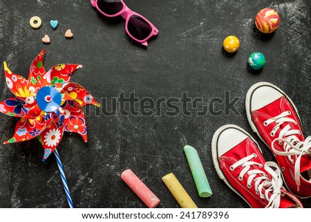 Toys and red sneakers on black chalkboard from above. Childhood - holiday or summer fun concept. Background layout with free text space. - stock photo
