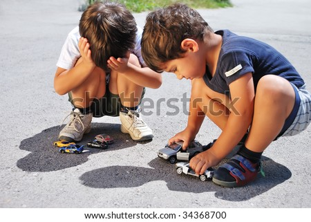 Toys cars in front of children legs - stock photo