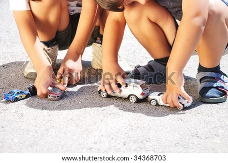 Toys cars in front of children legs