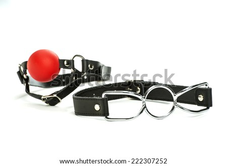 toys for bondage and role-playing: a spider-gag and a red ball-gag  - stock photo