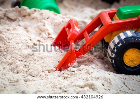 toys for kids in the sandbox, the tractor picks up the sand - stock photo
