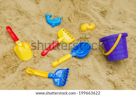Toys in the sand - shovel, stencils, rakes - stock photo